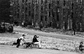 Young boys playing outside with homemade go-karts, pushing them down a hill in the run down Maryhill district of Glasgow in the summer of 1976 - John Sturrock - ,1970s,1976,bleak,boy,boys,child,childhood,children,cities,city,clearance,CLEARENCE,conditions,derelict,DERELICTION,EQUALITY,excluded,exclusion,flats,friend,friends,funny,Glasgow,go-kart,go-karts,HARD