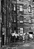 Woman hagning her washing to dry in the run down Maryhill district of Glasgow in the summer of 1976 - John Sturrock - ,1970s,1976,apparel,bleak,cities,city,clearance,CLEARENCE,clothes,clothing,conditions,derelict,DERELICTION,employee,employees,Employment,EQUALITY,excluded,exclusion,FEMALE,flats,Glasgow,HARDSHIP,house