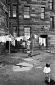 Child playing in a puddle whilst its parents hang their washing to dry in the run down Maryhill district of Glasgow in the summer of 1976. - John Sturrock - 1970s,1976,adult,adults,apparel,bleak,child,CHILDHOOD,children,cities,city,cleaning,cleansing,clearance,CLEARENCE,clothes,clothing,conditions,council estate,council services,council estate,council ser