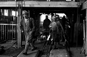Miners coming off shift at Cwm Coedely Colliery in the South Wales coalfields, 1976. - John Sturrock - 1970s,1976,change,Coal Industry,Coal Mine,coalfield,coalindustry,collieries,colliery,coming off,EBF,Economic,Economy,employee,employees,Employment,hard hats,helmet,helmets,job,jobs,LBR,male,man,men,mi