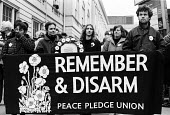 Remember and Disarm. Campaigners from the Peace Pledge Union with white poppies, Remembrance Sunday, London, 1987. - Lanre Fehintola - 1980s,1987,activist,activists,against,Anti War,Antiwar,banner,banners,CAMPAIGN,campaigner,Campaigners,CAMPAIGNING,CAMPAIGNS,DEMONSTRATING,demonstration,DEMONSTRATIONS,London,male,man,men,pacifism,paci