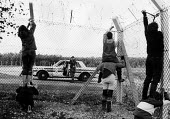 Greenham Common. Military police photograph women peace campaigners as they use bolt cutters to cut down the security fence at the US air base before entering the site as part of their protest campaig... - Melanie Friend - 1980s,1983,action,activist,activists,adult,adults,against,Air force,air forces,airforce,Anti War,anti-nuclear,Antiwar,armed forces,army,atomic,Barbed Wire,breach,camera,cameras,CAMPAIGN,Campaign for n