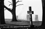 Cemetery with Windscale nuclear power plant in the distance behind it, 1977, Cumbria. - Mike Khan - &,1970s,1977,atomic,bare,belief,BNFL,branch,branches,capitalism,capitalist,Cemeteries,cemetery,chimney,chimneys,conviction,cross,death,DEATHS,died,EBF,Economic,Economy,ELECTRICAL,electricity,faith,gen