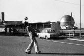 Worker playing with a football during a strike, Windscale nuclear power plant, 1977, Cumbria - Mike Khan - 1970s,1977,atomic,AUEW,BNFL,capitalism,capitalist,DISPUTE,DISPUTES,electricity generator,employee,employees,Employment,europeregi,fashion,flared jeans,flares,football,INDUSTRIAL DISPUTE,industrial rel