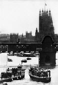 Sir Winston Churchill Funeral. Churchill's coffin, draped with the Union Jack flag, is transported aboard the Havengore from Westminster Pier to St Paul's Cathedral. - Michael Taylor - 1960s,1965,boat,boats,casket,Churchill,cities,city,coffin,funeral,FUNERALS,Houses,London,male,man,maritime,maritime industry,men,nautical,navy,of,Parliament,people,person,persons,Pier,POL,political,PO