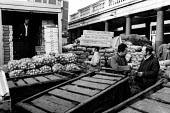 Covent Garden fruit and vegetable market, London, 1971. Covent Garden porter at work. - Mike Tull - 1970s,1971,and,barrow,barrows,by hand,carriage,CARRIAGES,carries,carry,carrying,cart,carts,cities,city,distributing,distribution,EARNINGS,EBF,Economic,Economy,employee,employees,Employment,FLOWER,flow