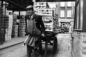 Covent Garden fruit and vegetable market, London, 1971. Covent Garden porter at work. - Mike Tull - 1970s,1971,and,barrow,by hand,cart,carts,cities,city,crate,crates,distributing,distribution,EARNINGS,EBF,Economic,Economy,employee,employees,Employment,FLOWER,flowering,flowers,food,FOODS,fresh,fruit,