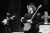 Richard's Cork Leg by Brendan Behan with Irish folk band, The Dubliners, Royal Court Theatre, London, 1972. Luke Kelly and Barney MacKenna, in background. - Patrick Eagar - 1970s,1972,ACE,act,acting,actor,actors,arts,band,bands,banjo,banjos,cities,city,Court,culture,drama,DRAMATIC,entertainment,instruments,Irish,London,maker,makers,making,male,man,melody,men,music,MUSICA