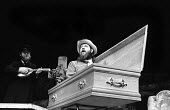 Richard's Cork Leg by Brendan Behan with Irish folk band, The Dubliners, Royal Court Theatre, London, 1972. Ciaron Bourke, in coffin, and John Sheehan. - Patrick Eagar - 1970s,1972,ACE,act,acting,actor,actors,arts,band,bands,banjo,banjos,casket,cities,city,coffin,Court,culture,drama,DRAMATIC,entertainment,instruments,Irish,London,maker,makers,making,male,man,melody,me