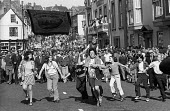 Durham Miners Gala, 1974. Following tradition, families and children from the pit villages dance in the street in front of their Lodge banner as it is paraded in the annual Big Meeting. - Angela Phillips - 14-07-1974