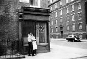 Young couple hugging on a street, West End in the early 1960's London - Romano Cagnoni - ,&,1960s,1962,adult,adults,boy,boyfriend,BOYFRIENDS,BOYS,child,CHILDHOOD,children,cities,city,corner,couple,COUPLES,EMBRACE,EMBRACING,EMOTION,EMOTIONAL,EMOTIONS,female,females,girl,girlfriend,girlfrie