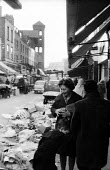 Exmouth Market street market in the then borough of Finsbury, now Islington, in the early 1960's. On the left is the tower of the Holy Redeemer Church. .... - Romano Cagnoni - 1960s,1964,adult,adults,boy,boys,buy,buyer,buyers,buying,child,CHILDHOOD,children,cities,city,commerce,commodities,commodity,EBF,Economic,economy,families,FAMILY,FEMALE,goods,Islington,juvenile,juveni