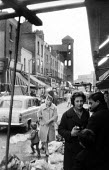 Exmouth Market street market in the then borough of Finsbury, now Islington, in the early 1960's. On the left is the tower of the Holy Redeemer Church. .... - Romano Cagnoni - 1960s,1964,adult,adults,boy,boys,buy,buyer,buyers,buying,child,CHILDHOOD,children,cities,city,commerce,commodities,commodity,communicating,communication,conversation,conversations,dialogue,discourse,d
