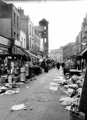 Exmouth Market street market in the then borough of Finsbury, now Islington, in the early 1960's. On the left is tower of the Holy Redeemer Church and in the distance Mount Pleasant Sorting Office. ..... - Romano Cagnoni - 1960s,1964,cities,city,commerce,EBF,Economic,economy,Islington,litter,London,market,markets,REFUSE,rubbish,run-down,scene,scenes,SERVICE,SERVICES,Sorting,stall,stalls,street,streets,trader,traders,tra
