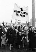 Women Against The Bomb join the traditional CND march. Easter protest against nuclear arms, London 1965 - Romano Cagnoni - 1960s,1965,activist,activists,adult,adults,Against,Anti Nuclear weapons,Anti War,Antiwar,atomic,banner,banners,Bomb,BOMBS,boy,boys,Campaign,Campaign for Nuclear Disarmament,campaigner,campaigners,CAMP