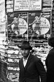 Street scene in Lisbon, Portugal. Man with a movie poster for the film Las 4 bodas de Marisol, 1968. - Romano Cagnoni - 06-03-1968