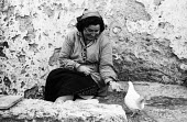Street scene in Lisbon, Portugal in 1968. Woman feeding bird. - Romano Cagnoni - 06-03-1968