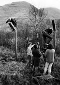 Members of Faslane Peace Camp in Scotland take non-violent direct action by entering Glen Douglas armaments depot- a NATO defence munitions depot- by climbing over the security fence to plant flower b... - Rick Matthews - 1980s,1983,action,activist,activists,against,Anti War,anti-nuclear,Antiwar,armed forces,Barbed Wire,breach,bulbs,Camp,CAMPAIGN,Campaign for nuclear disarmament,campaigner,campaigners,CAMPAIGNING,CAMPA