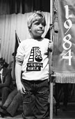 Scottish rally in support of the miners strike. Young boy wears a sweat shirt with the words My dad is a striking miner, designed by Lucy Morrison NALGO - Rick Matthews - 1980s,1984,activist,activists,against,banner,banners,boy,boys,CAMPAIGN,campaigner,campaigners,CAMPAIGNING,CAMPAIGNS,child,CHILDHOOD,children,DEMONSTRATING,demonstration,DEMONSTRATIONS,disputes,familie
