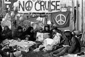 Women at the Greenham Common Peace Camp in Newbury, Berkshire, reading a story in the Daily Mail about their protest against US air bases hosting nuclear weapons in the UK whilst blockading a gate. - Stefano Cagnoni - 1980s,1982,action,activist,activists,against,anti,Anti Nuclear weapons,Anti War,Antiwar,atomic,balloon,balloons,banner,banners,blockade,blockading,blocking,Camp,CAMPAIGN,Campaign for Nuclear Disarmame