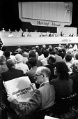 Labour Party delegate reading newspaper with British Petroleum (BP) shares advertisement as the nationalised oil idustry is privatised, Labour Party Conference, Blackpool, 1987 - Stefano Cagnoni - 1980s,1987,advert,ADVERTISED,advertisement,advertisements,advertising,ADVERTISMENT,adverts,Ahead,BP,Conference,conferences,delegate,DELEGATES,Labour Party,male,man,men,Moving,newspaper,newspapers,oil,