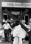 London Procession in Honour of Our Lady of Mount Carmel: A figure dressed as Jesus and carrying a wooden cross passes the Guardian Newspaper building during the annual Italian religious procession thr... - Stefano Cagnoni - 15-07-1989