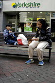 A woman and her son, town centre, Liverpool. - Rob Bremner - 2000s,2004,adult,adults,asian,bag,bags,black,BME Black minority ethnic,boy,boys,building,building society,BUILDINGS,child,CHILDHOOD,children,cities,city,consumer,consumers,crisp,customer,customers,eat