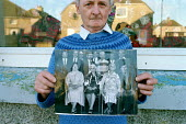 A retired man holding a old photograph of his family, outside his house in Caithness. - Rob Bremner - 1990s,1999,adult,adults,age,ageing population,building,buildings,elderly,families,family,FEMALE,hold,holding,home,homes,house,houses,housing,image,images,lfL lifestyle & leisure,male,man,MATURE,memori