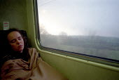 A woman sleeping on a train, while traveling to Wick in Northern Scotland. - Rob Bremner - 1990s,1999,asleep,carriage,carriages,coat,coats,country,countryside,exhausted,EXHAUSTION,female,females,girl,girls,journey,journeys,landscape,landscapes,lfL lifestyle & leisure,network,outdoors,outsid