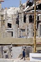 Schoolboy passing the destroyed camp of Nahr al-Bared Palestinian refugee camp - Ron Coelle - ,2000s,2007,2008,Agency,ahr al Bared,ahr el-Bared,aid agency,al-Bared,and,assistance,boy,boys,broken,building,buildings,camp,camps,child,CHILDHOOD,children,conflict,crisis,destroyed,destruction,Diaspo
