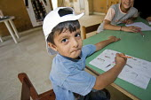 Child drawing in a temporary classroom, at Nahr al-Bared Palestinian refugee camp. - Ron Coelle - 2000s,2008,activities,agencies,Agency,ahr al Bared,ahr el-Bared,aid,aid agency,al-Bared,and,art,assistance,baseball cap,book,books,boy,boys,camp,camps,caps,charitable,charities,charity,child,CHILDHOOD
