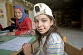 Children in a temporary classroom, at Nahr al-Bared Palestinian refugee camp. - Ron Coelle - 2000s,2007,2008,activities,agencies,Agency,ahr al Bared,ahr el-Bared,aid,aid agency,al-Bared,and,art,assistance,baseball cap,book,books,burn,burning,BURNS,burnt,camp,camps,caps,charitable,charities,ch