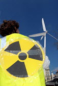 Anti nuclear protest against the construction by EDF of a reactor EPR Flamanville, France. The protestor is holding a model wind turbine symbolic of renewable energy. - Stephane AUDRAS - 17-03-2007