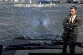 A Bus driver with the broken windscreen of a bus after an attack inwhich paving stones were thrown breaking the glass. Burden, France. - Marta NASCIMENTO - 24-09-1998