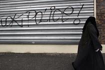 Urban violence, La Madeleine district, Normandy. Shop shut down, inscription, graffiti against the police on the metal shutter, slogan in English Fuck Police, Muslim woman wearing an Islamic veil - Marta NASCIMENTO - 2000s,2005,adult,adults,against,bigotry,BME Black minority ethnic,crs,DISCRIMINATION,dress,equal,equality,estate,estates,eu,Europe,european,europeans,FEMALE,french,graffiti,hajib,headscarf,hijab,Housi