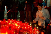A Spanish woman lights a candle to mourn the victims of the terrorist bombing of commuter trains on the morning of 11 March 2004, between Alcal de Henares and Atocha station in Madrid, which killed 19... - Mario Fourmy - 11-03-2004