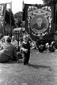 Child playing infront of trades union banners. Durham Miners Gala 1974. - Roy Peters - 22-07-1974