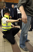 A policeman searches a young man during an operation to police fare evasion and anti social behaviour on the transport network at Kensal Green Station in North West London. Officers from the British T... - Rogan Macdonald - ,2000s,2007,adult,adults,and,anti social behaviour,anti-knife,avoiding,behavior,behaviour,British Transport Police,carries,carry,carrying,CLJ crime,detecting,detector,detectors,dodger,dodgers,evading,
