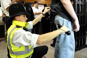A policeman searches a young man during an operation to police fare evasion and anti social behaviour on the transport network at Kensal Green Station in North West London. Officers from the British T... - Rogan Macdonald - 2000s,2007,adult,adults,and,anti social behaviour,anti-knife,avoiding,behavior,behaviour,British Transport Police,carries,carry,carrying,CLJ crime,detecting,detector,detectors,dodger,dodgers,evading,e