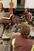 Emergency Response Unit (ERU) and firefighters practise removing a person from under a train. The ERU works in conjunction with the emergency services in responding to derailments and accidents on the... - Rogan Macdonald - (ERU),2000s,2006,adult,adults,attention,attentive,bodies,body,cities,city,communicating,communication,dia accident accidents,emergency,Fire and Rescue,fire brigade,fire service,firefighter,firefighter