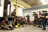 Firefighters being debriefed by a member of the Emergency Response Unit (ERU) after practising the removal of a person from under a train. The ERU works in conjunction with the emergency services in r... - Rogan Macdonald - (ERU),2000s,2006,adult,adults,attention,attentive,carriage,carriages,cities,city,communicating,communication,conversation,debriefing,dia accident accidents,dialogue,emergency,Fire and Rescue,fire brig