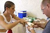 Trainer, Peter Martin, with the boxer, Shanee Martin, before a fight for the British Masters Female Super Flyweight Title, At Goresbrook Leisure Centre in Dagenham, London. - Rogan Macdonald - 2000s,2006,bandage,bandages,bandaging,bout,bouts,box,boxer,boxers,boxes,Boxing,Boxing Match,braid,braided,check,checking,classes,combat,Dagenham,dressing,dressings,EXERCISE,exercises,exercising,female
