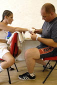 Trainer, Peter Martin, with the boxer, Shanee Martin, before a fight for the British Masters Female Super Flyweight Title, At Goresbrook Leisure Centre in Dagenham, London. - Rogan Macdonald - 2000s,2006,arm,arms,bandaging,bout,bouts,boxer,boxers,Boxing,Boxing Match,braid,braided,chair,chairs,check,checking,classes,combat,Dagenham,EXERCISE,exercises,exercising,female,females,fight,fighter,f