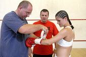 Trainer, Peter Martin, with the boxer, Shanee Martin, before a fight for the British Masters Female Super Flyweight Title, At Goresbrook Leisure Centre in Dagenham, London. - Rogan Macdonald - 2000s,2006,adhesive,bout,bouts,boxer,boxers,boxing,Boxing Match,braid,braided,classes,combat,Dagenham,EXERCISE,exercises,exercising,female,females,fight,fighter,fighters,fist,fists,Flyweight,glove,glo