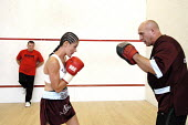 Trainer, Terry Coulter, sparring with the boxer, Shanee Martin, before a fight for the British Masters Female Super Flyweight Title, At Goresbrook Leisure Centre in Dagenham, London. - Rogan Macdonald - 2000s,2006,bout,bouts,boxer,boxers,boxing,Boxing Match,braid,braided,classes,combat,Dagenham,EXERCISE,exercises,exercising,female,females,fight,fighter,fighters,fist,fists,Flyweight,glove,gloves,gym,g