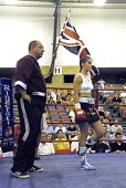 Boxer, Shanee Martin, enters the ring for the fight for the British Masters Female Super Flyweight Title, At Goresbrook Leisure Centre in Dagenham, London. - Rogan Macdonald - (WSO),2000s,2006,audience,audiences,bout,bouts,boxer,boxers,boxing,Boxing Match,boxing ring,braid,braided,British,chair,chairs,classes,combat,Council,Dagenham,entertainment,event,events,face,faces,fem