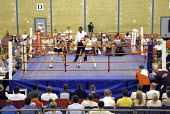 Woman boxer Shanee Martin (white top), fighting Juliette Winters, (black top) for the British Masters Female Super Flyweight Title. At Goresbrook Leisure Centre in Dagenham, London. - Rogan Macdonald - (WSO),2000s,2006,audience,audiences,BAME,BAMEs,bme,BME Black minority ethnic,bmes,bout,bouts,boxer,boxers,boxing,Boxing Match,boxing ring,braid,braided,British,chair,chairs,classes,combat,Council,Dage