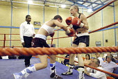 Woman boxer Shanee Martin (white top) fighting Juliette Winters (black top) for the British Masters Female Super Flyweight Title, At Goresbrook Leisure Centre in Dagenham, London. - Rogan Macdonald - (WSO),2000s,2006,audience,audiences,BAME,BAMEs,bme,BME Black minority ethnic,bmes,bout,bouts,boxer,boxers,boxing,Boxing Match,boxing ring,braid,braided,British,chair,chairs,cities,city,classes,combat,