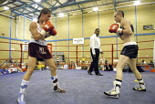 Woman boxer Shanee Martin (white top) fighting Juliette Winters (black top) for the British Masters Female Super Flyweight Title, At Goresbrook Leisure Centre in Dagenham, London. - Rogan Macdonald - (WSO),2000s,2006,audience,audiences,BAME,BAMEs,bme,BME Black minority ethnic,bmes,bout,bouts,boxer,boxers,boxing,Boxing Match,boxing ring,braid,braided,British,classes,combat,Council,Dagenham,diversit