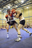 Woman boxer Shanee Martin (white top) fighting Juliette Winters (black top) for the British Masters Female Super Flyweight Title, At Goresbrook Leisure Centre in Dagenham, London. - Rogan Macdonald - (WSO),2000s,2006,audience,audiences,bout,bouts,boxer,boxers,boxing,Boxing Match,boxing ring,braid,braided,British,classes,combat,Council,Dagenham,entertainment,event,events,face,faces,female,females,f